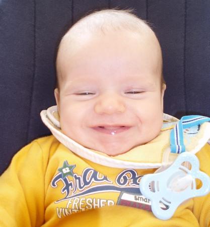 lachendes Baby in gelbem Pullover