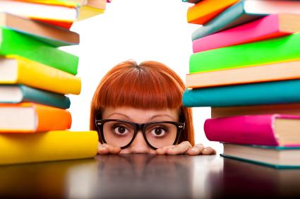 Mädchen zwischen 2 Stapeln bunte Bücher